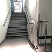 grijze plaeautraplift onder aan trap opgeklapt